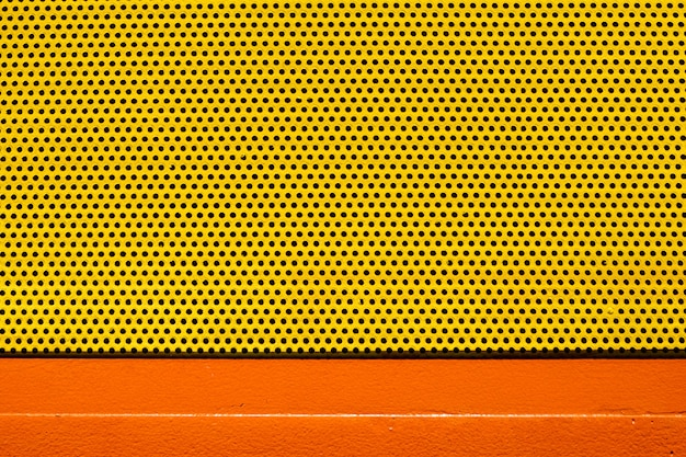Pomarańczowy żółty kolor blachy z wieloma małymi okrągłymi otworami kropkuje teksturę tła