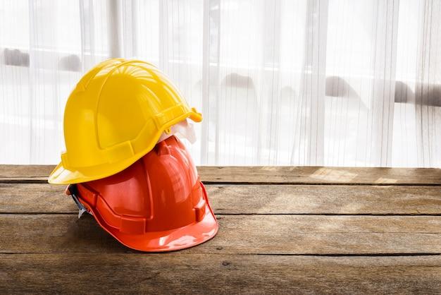 Pomarańczowy, żółty twardy kask budowy kapelusz do projektu bezpieczeństwa robotnika jako inżynier lub pracownik