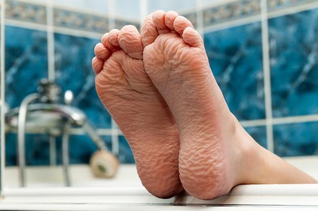 Pomarszczone bose stopy wychodzące z wanny.