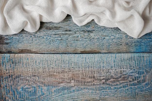 Pomarszczony biały materiał na starej malowanej desce