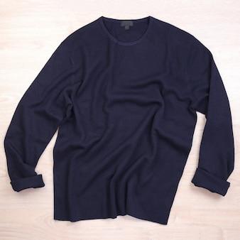 Pomarszczony niebieski granatowy sweter na drewnianej podłodze