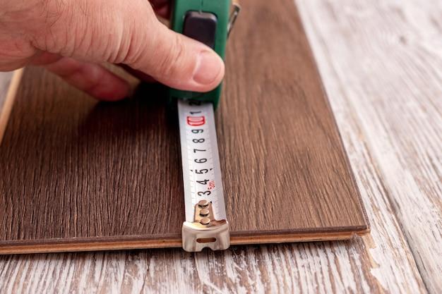 Pomiar długości deski za pomocą taśmy mierniczej