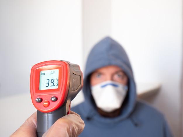 Pomiar temperatury człowieka za pomocą miernika podczerwieni. wysoka gorączka, objaw, choroba.