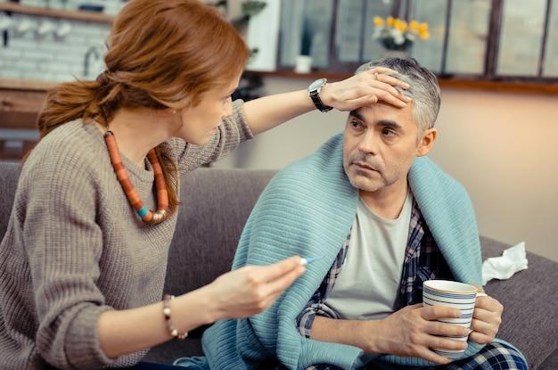 Pomiar temperatury. miła, opiekuńcza kobieta dotykająca czoła męża, siedząc obok niego