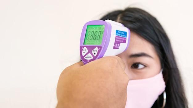 Pomiar temperatury za pomocą termometru na podczerwień młodej kobiety w masce na twarz w punkcie kontrolnym na białym tle
