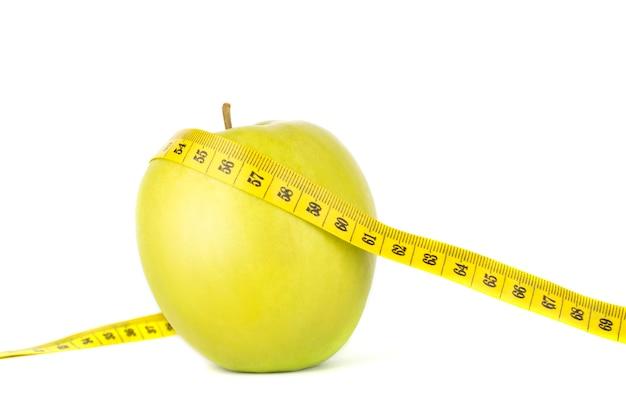 Pomiarowa taśma i zieleni jabłko na białym odosobnionym tle.