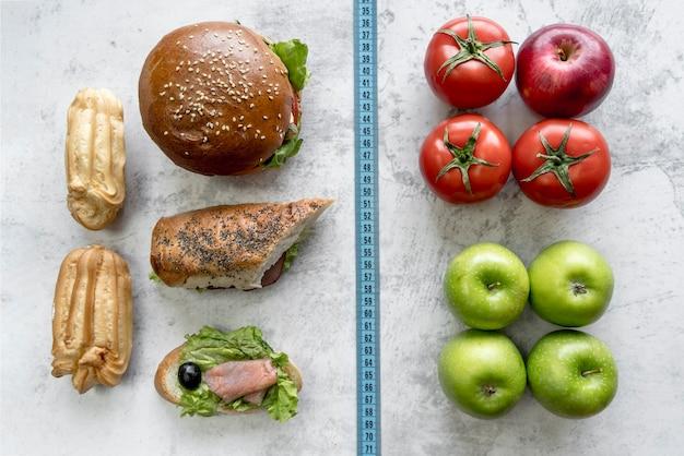 Pomiarowa taśma między zdrowym i niezdrowym jedzeniem nad betonowym tłem