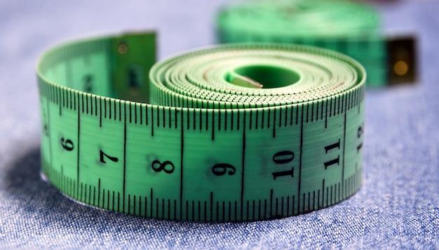 Pomiarowa taśma na niebieskiej dżinsy tkaniny teksturze z selekcyjną ostrością szycia lub ciężaru kontrola pojęcie.