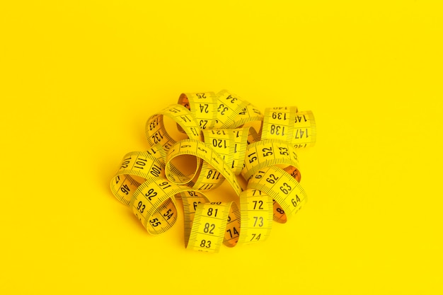 Pomiarowa taśma na żółtym tle. miara w kształcie spirali skręconej na żółtym tle. odchudzanie i dieta koncepcja, miejsce