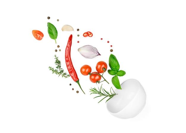 Pomidor, bazylia, przyprawy, papryczka chili, świeży tymianek czosnkowy, cebula latająca. wegańskie jedzenie dietetyczne na białym tle.
