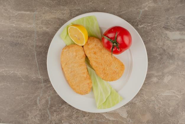Pomidor, cytryna, bryłki kurczaka na białym talerzu.