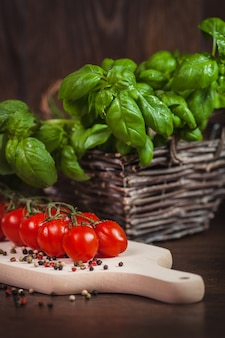 Pomidor czereśniowy i zielone świeże zioła na drewnie