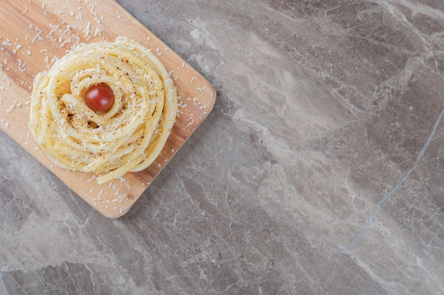 Pomidor i makaron na desce do krojenia, na marmurowej powierzchni.