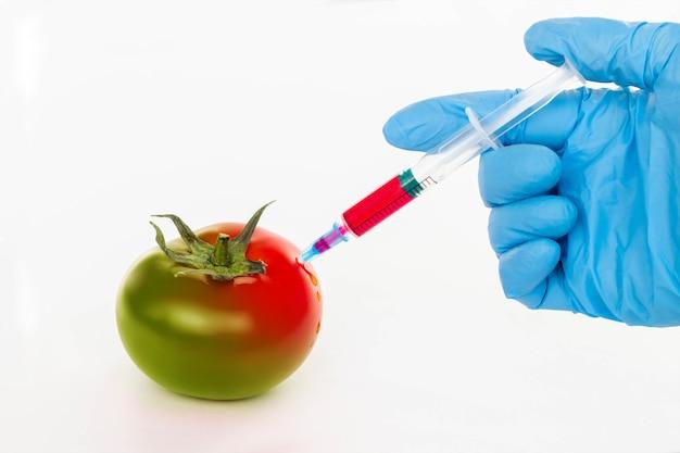 Pomidor i strzykawka z azotanami na białym tle na białym tle.