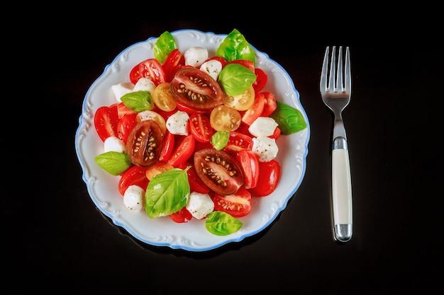 Pomidor koktajlowy z serem mozzarella na białym talerzu widelcem.