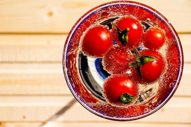 Pomidor pływa w wodzie z bąbelkami w szklanym szkle na białym tle.