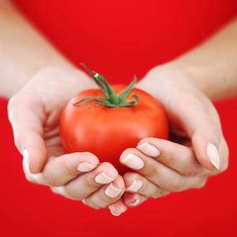 Pomidor w rękach kobiety