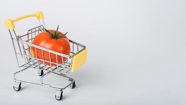 Pomidor w wózek na zakupy na białej powierzchni
