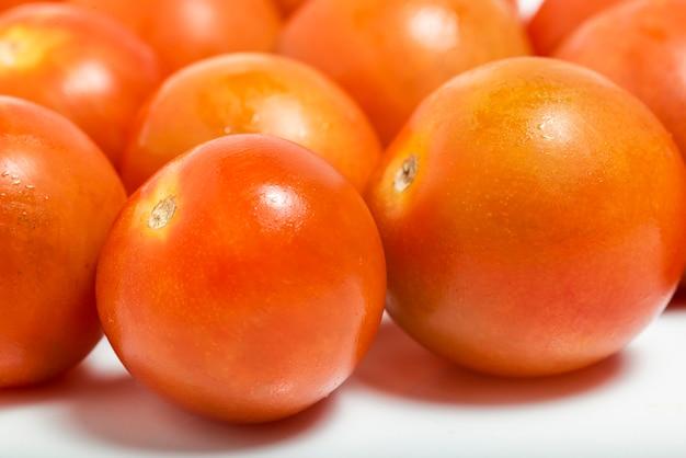 Pomidor wiśniowy z bliska na białym tle. fotografia makro.