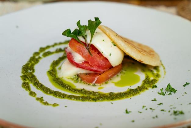 Pomidor z serem cheddar, tostem chlebowym i sosem pesto na talerzu - kuchnia wegańska i warzywna