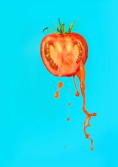 Pomidor z sokiem pomidorowym lub keczupem na niebieskim tle