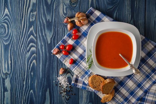 Pomidorowa polewka i świezi pomidory na drewnianym stole, odgórny widok