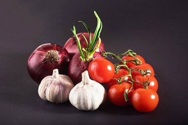 Pomidory, cebula i czosnek są odizolowane na czarno