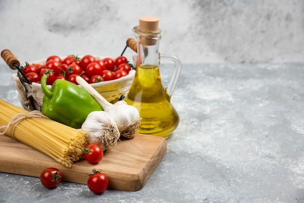 Pomidory czereśniowe, makarony, czosnek, zielony pieprz i oliwa z oliwek na drewnianej desce.