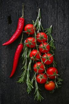 Pomidory czereśniowe na gałąź z rozmarynem i chili na zmroku.