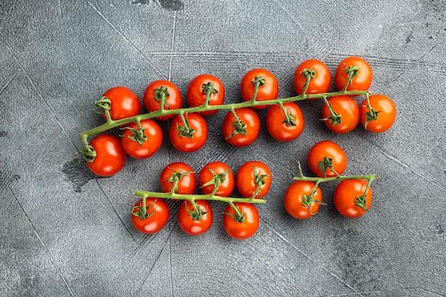 Pomidory czereśniowe na zestawie winorośli, na szarym tle kamienia, widok z góry na płasko