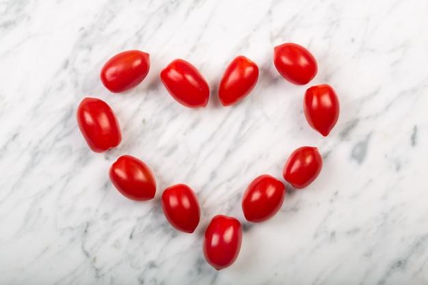 Pomidory czereśniowe ułożone w kształcie serca na białym tle z marmuru