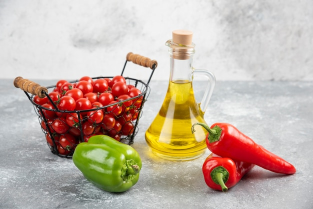 Pomidory czereśniowe w koszu z papryczkami chili i oliwą z oliwek.