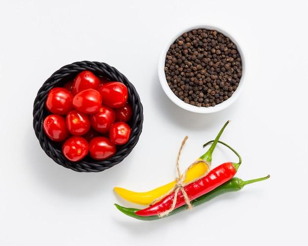 Pomidory czereśniowe w koszu z pieprzem ziele angielskie i ostrym chili na białym tle. widok z góry świeżych warzyw.