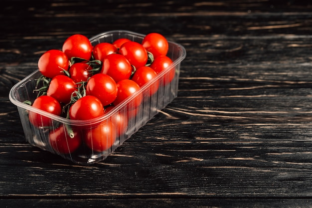 Pomidory czereśniowe w plastikowym pudełku na drewnianym stole