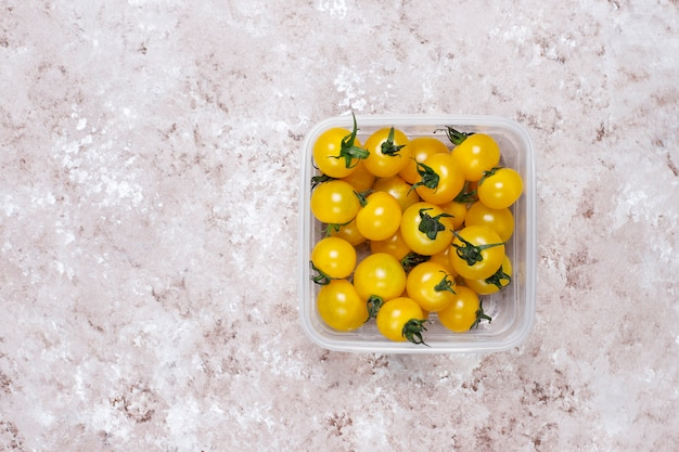 Pomidory czereśniowe w różnych kolorach, żółte i czerwone pomidory czereśniowe na jasnym tle