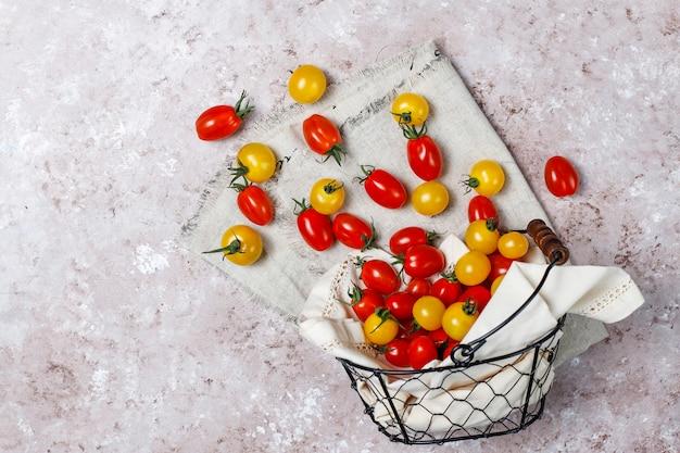 Pomidory czereśniowe w różnych kolorach, żółte i czerwone pomidory czereśniowe w koszu na jasnym tle