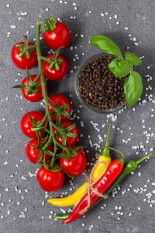 Pomidory czereśniowe z bazylią, pieprzem ziela angielskiego, ostrym chilli i solą na szarym tle. widok z góry świeżych warzyw.