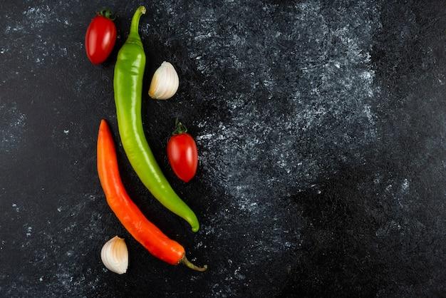 Pomidory, czosnek i papryczki chili na marmurowej powierzchni.