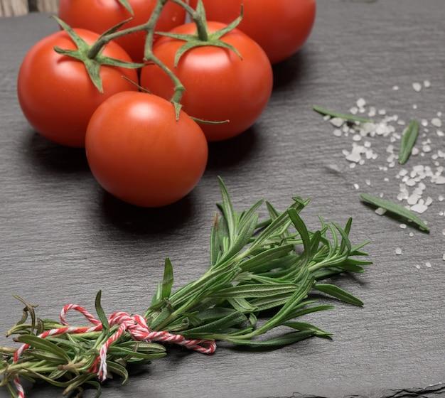Pomidory fred i świeża gałązka rozmarynu z zielonymi liśćmi na czarnej powierzchni, aromatyczna przyprawa