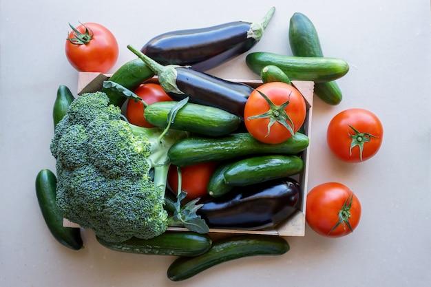 Pomidory i bakłażany, ogórki i brokuły w drewnianej skrzyni