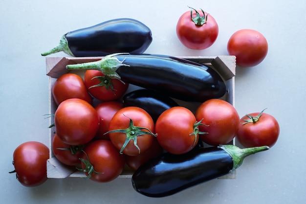 Pomidory i bakłażany w drewnianej skrzyni