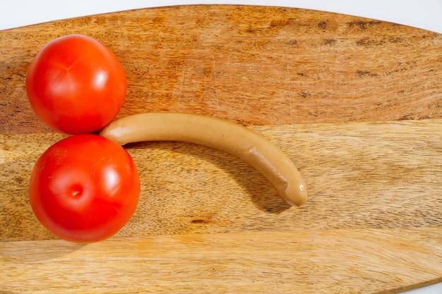 Pomidory i kiełbasa w postaci męskiego penisa na drewnianej desce do krojenia