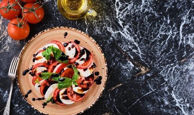 Pomidory i mazzarella, włoska sałatka caprese z pomidorami, mozzarellą, bazyliowym octem balsamicznym i oliwą z oliwek. ciemna marmurowa ściana, widok z góry, danie wegetariańskie