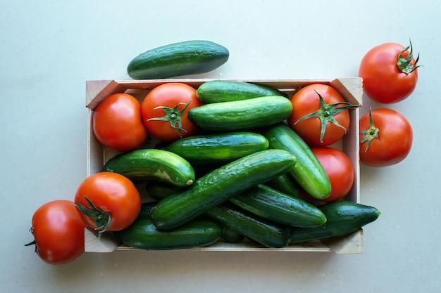 Pomidory i ogórki w drewnianej skrzyni