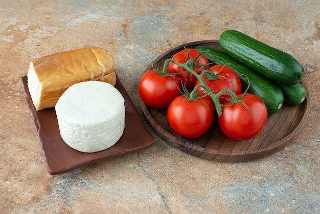 Pomidory i ogórki z serem na marmurowym stole.