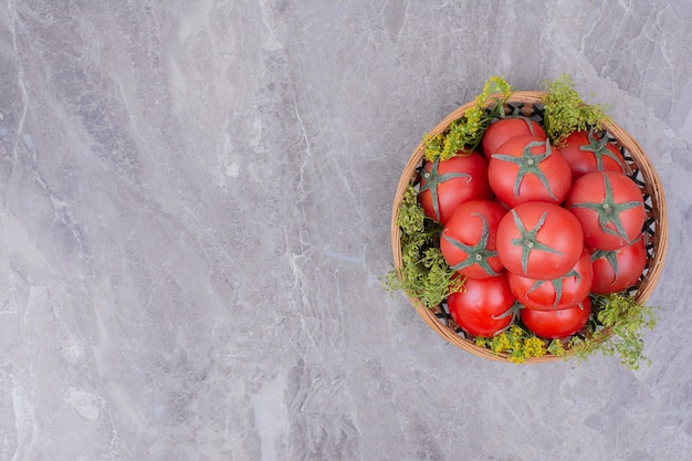 Pomidory izolowane w drewnianym talerzu na marmurze