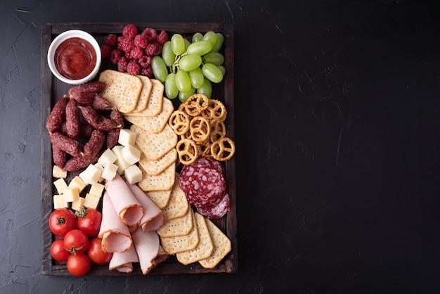 Pomidory, kiełbasa, owoce, krakersy i ser na desce wędlin na czarnym tle, przekąski na imprezę, zbliżenie.