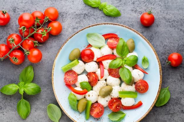 Pomidory koktajlowe, ser mozzarella, bazylia i przyprawy na szarej tablicy łupkowej. składniki sałatki włoskiej tradycyjnej caprese. jedzenie środziemnomorskie.