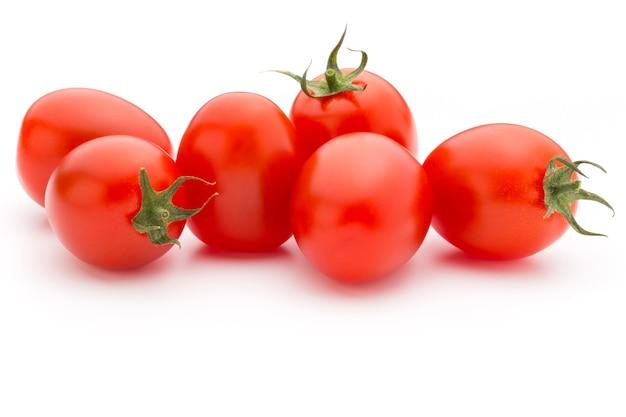 Pomidory koktajlowe. trzy pomidory czereśniowe na białej powierzchni.