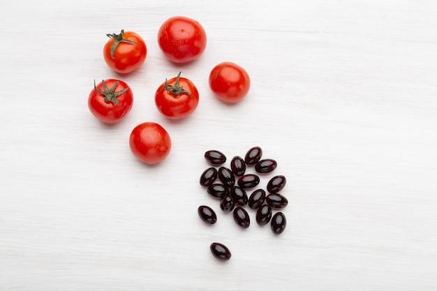 Pomidory leżą na białym stole obok witamin w postaci galaretki na białym stole. pojęcie witamin i minerałów.